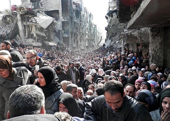 Besieged Palestinian refugees from Yarmouk camp line up for UN aid