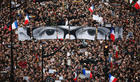 Charlie Hebdo editor Charb__039_s bespeckled eyes held aloft at growing ParisMarch demo_001.jpg