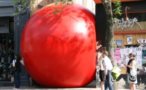 A giant red ball wedged between two buildings.