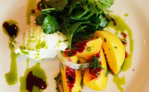 A salad with peaches, goat cheese, and tender greens.