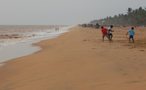 People playing football on a beach in overcast weather.