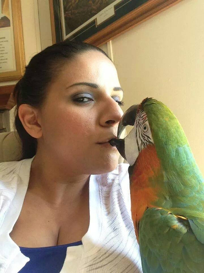 A woman kissing her parrot.