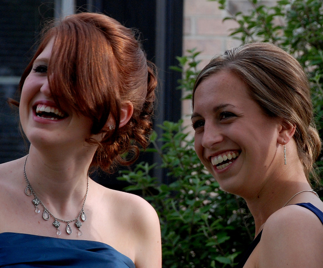 Two girls laughing and smiling at a prom photoshoot.