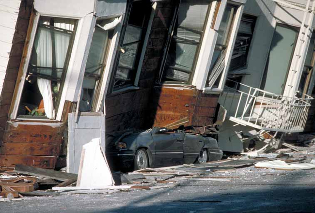 A car crushed under a row of Edwardian houses in San Francisco.
