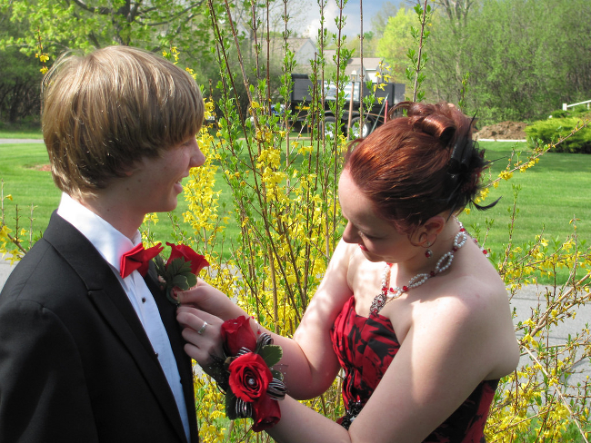 A girl pinning flowers onto her partner's suit.