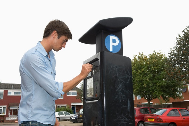 Side profile of a young man using a parking meter in a parking lot