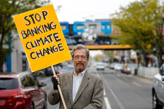 A protester holding up a STOP BANKING CLIMATE CHANGE sign