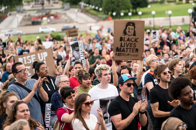 A mixed race crowd holding black lives matter signs and looking grim.