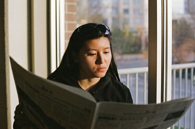 A person reading a newspaper.