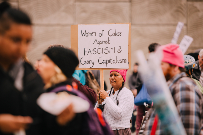 A woman holding a sign: Women of color against fascism and crony capitalism.