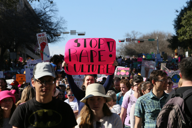 A protester holding a sign that says STOP RAPE CULTURE
