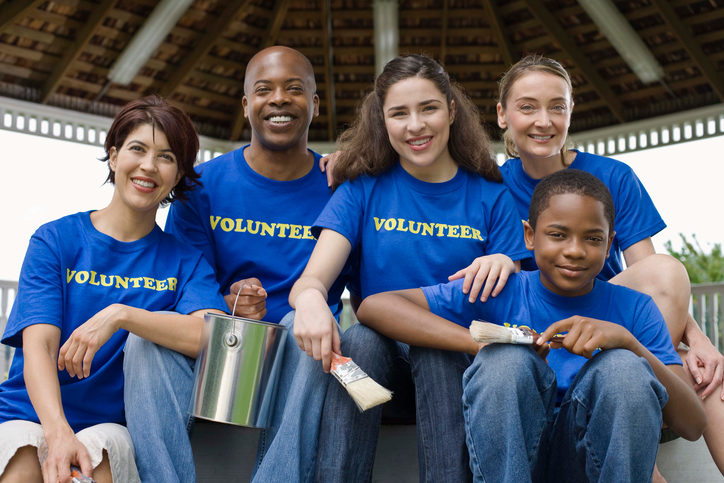 Portrait of volunteers holding painting supplies