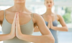 Two young girls meditating with hands joined