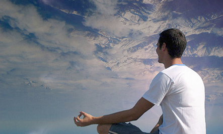Man meditating on a mountain.