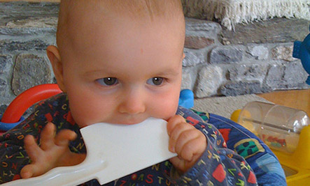 baby chewing on plastic spatula