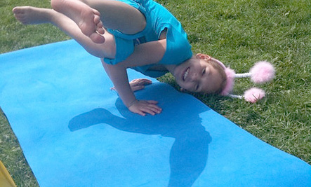 Little girl wearing bunny ears on a yoga mat