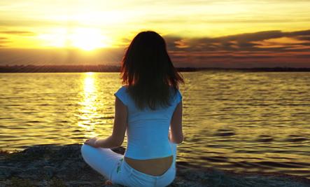 A woman meditating at sunset