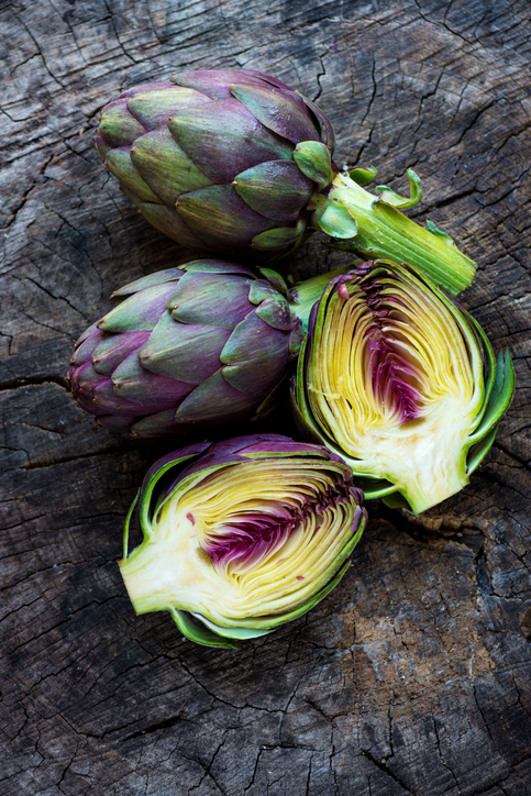 Organic Artichokes on  rustic wooden board