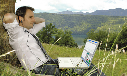Man with computer by sitting by tree