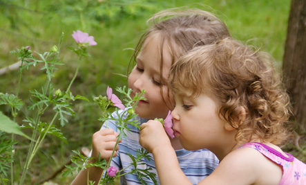 Two girls smelling flowers