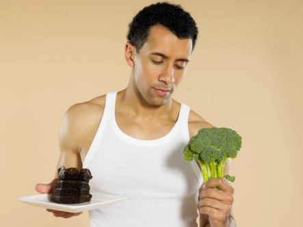 healthy man looking at cake and brocoli