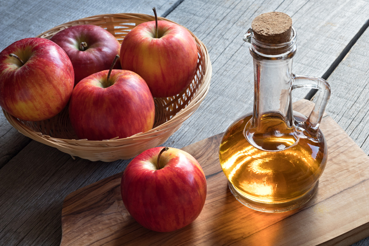 A bottle of apple cider vinegar with apples