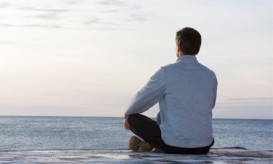 man mediating on beach