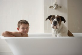 dog and boy in bathtub
