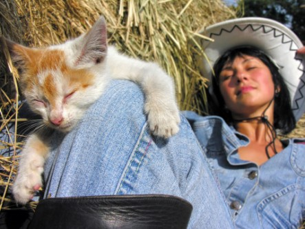woman girl cat pet pets ginger cat on girls knee sleeping cowboy cowgirl