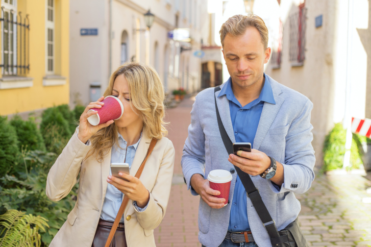 Couple checking smartphones while walking instead of talking to each other - tech addiction.