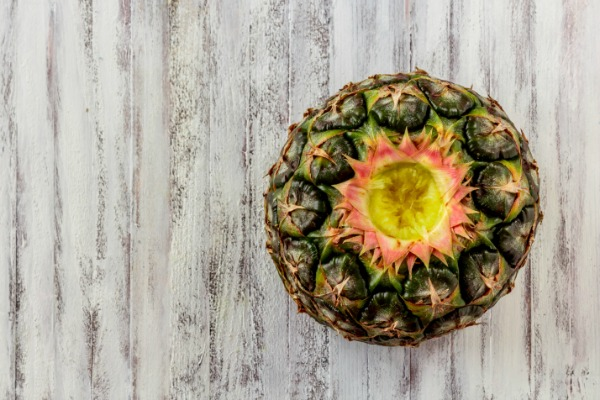 Half of a pineapple on a white background