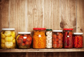 Preserved  autumn vegetables on shelf near a wooden wall