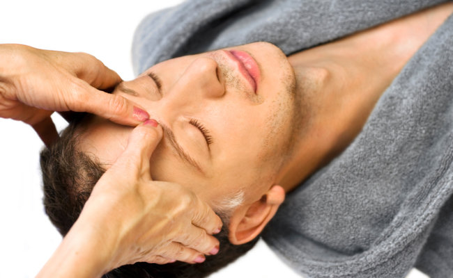 man lying, gets massage, reiki,acupressure on his face