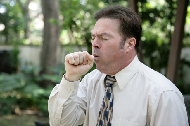 A man in a business suit coughing