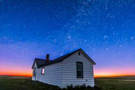 Star trails over Butala Homestead in OMB at dawn, SK (Photo by Alan Dyer)
