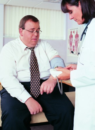 Overweight Businessman Having his Blood Pressure Taken by a Doctor