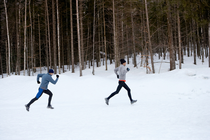 Two men running through snow, side view