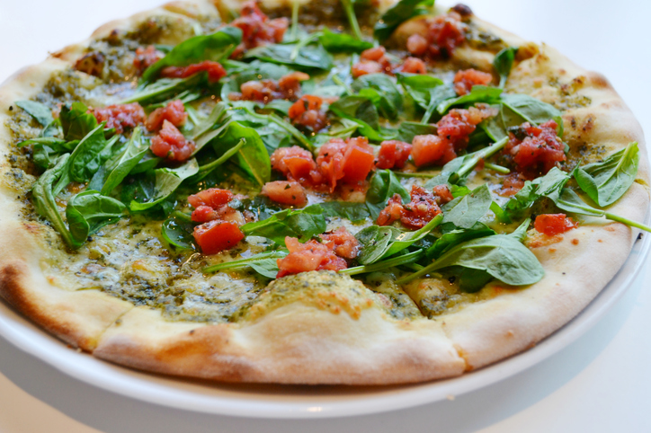 Big round vegetarian pizza with tomatoes and basil