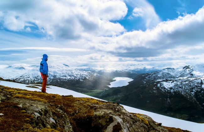 Tourist stands on a hilltop and look at the lake in the valley. Blue sky with clouds. Snowy mountains. Sunlight breaks through the clouds. Norway.