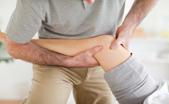 Chiropractor massaging a patient's knee
