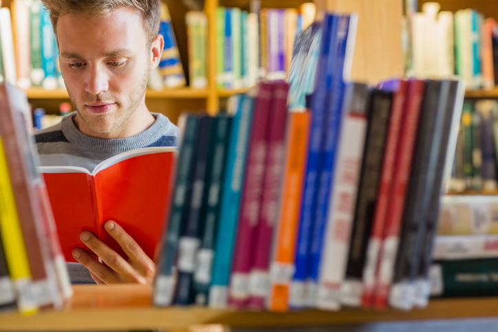 Male student reading book in the library