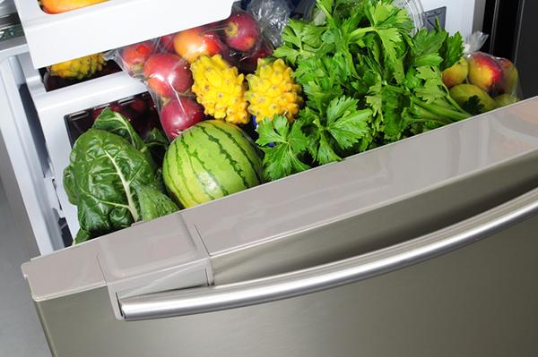 Fresh fruit and vegetables in salad drawer of refrigerator.