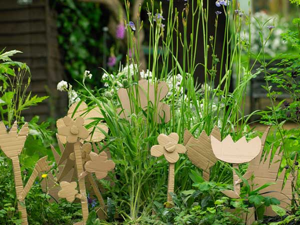 These cardboard flowers may not last, but there is a really cool and practical way to reuse leftover shipping boxes in your garden!