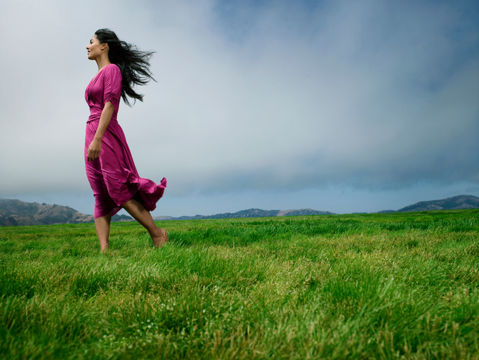 Woman standing in field barefoot