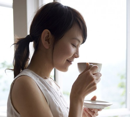 Woman drinking tea by window in home