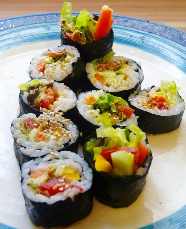 vegan sushi on a white plate with a blue border