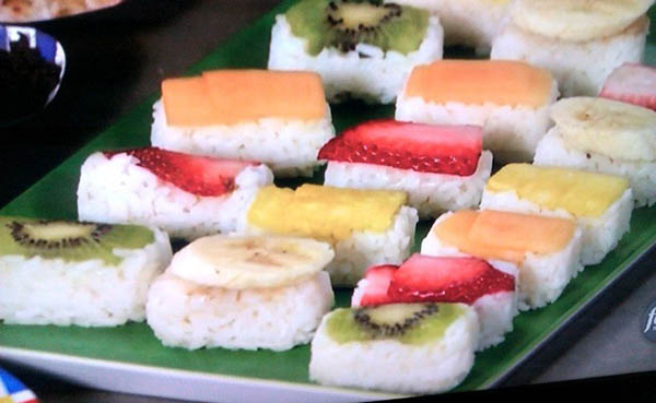 an array of fruit sushi on a green tray - kiri, strawberry, mango, banana, and pineapple