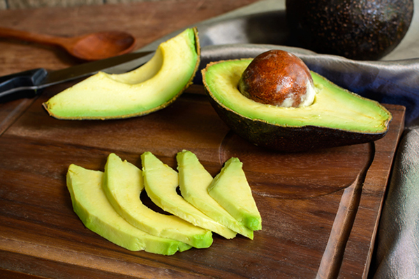 ripe slice avocado on wooden cutting board