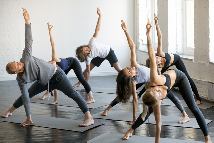 Group of young sporty people in extended triangle pose