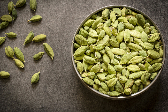 green cardamom pods in  steel bowl